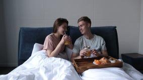 Pares jovenes que comparten el desayuno en cama en casa almacen de metraje de vídeo