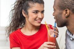 Pares jovenes que comparten el vidrio de zumo de naranja Fotos de archivo