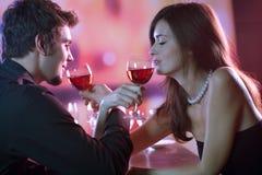 Pares jovenes que comparten un vidrio de vino rojo en el restaurante, celebrat Fotografía de archivo libre de regalías