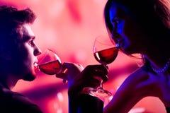 Pares jovenes que comparten un vidrio de vino rojo en el restaurante, celebrat Fotografía de archivo