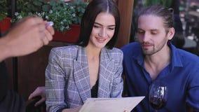 Pares jovenes que comparten un vidrio de vino rojo en el restaurante, celebrat Gente con el menú que hace orden en el café almacen de video
