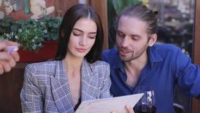 Pares jovenes que comparten un vidrio de vino rojo en el restaurante, celebrat Gente con el menú que hace orden en el café metrajes
