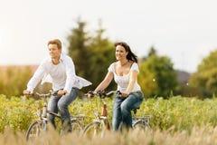 Pares jovenes que completan un ciclo con la bicicleta en verano imagen de archivo libre de regalías