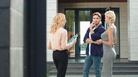 Pares jovenes que compran la casa de lujo junto Agente de la propiedad inmobiliaria que aconseja la casa para juntarse almacen de video
