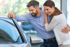 Pares jovenes que compran un coche Imagen de archivo libre de regalías