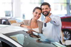 Pares jovenes que compran un coche Fotografía de archivo libre de regalías