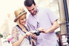 Pares jovenes que comprueban imágenes en su cámara Imagen de archivo libre de regalías
