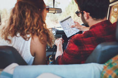 Pares jovenes que comprueban un mapa en roadtrip Fotos de archivo