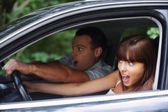 Pares jovenes que conducen el coche Imágenes de archivo libres de regalías
