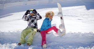 Pares jovenes que consiguen listos para ir snowboard fotos de archivo libres de regalías