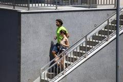 Pares jovenes que corren abajo de las escaleras en el ambiente urbano Fotografía de archivo libre de regalías