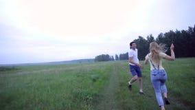Pares jovenes que corren en el campo con una cometa almacen de video