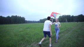 Pares jovenes que corren en el campo con una cometa almacen de metraje de vídeo