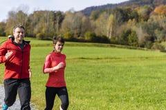Pares jovenes que corren en el día soleado en el bosque del otoño del th Fotos de archivo libres de regalías