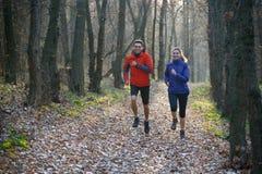 Pares jovenes que corren en el rastro en el bosque salvaje Imagen de archivo libre de regalías