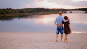 Pares jovenes que corren en la arena en la playa al lago pintoresco del bosque en la puesta del sol almacen de metraje de vídeo