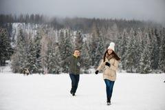 Pares jovenes que corren en la nieve, divirtiéndose Imagen de archivo