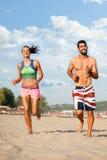 Pares jovenes que corren en la playa Foto de archivo libre de regalías