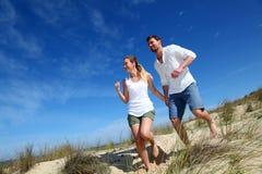 Pares jovenes que corren en la playa arenosa Imagen de archivo libre de regalías
