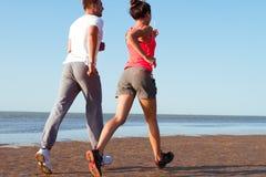 Pares jovenes que corren junto al lado del agua en la playa Hombre Imagenes de archivo