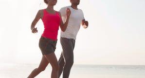 Pares jovenes que corren junto al lado del agua en la playa Hombre Fotografía de archivo