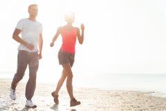 Pares jovenes que corren junto al lado del agua en la playa Hombre Fotografía de archivo libre de regalías