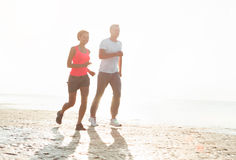 Pares jovenes que corren junto al lado del agua en la playa Hombre Imágenes de archivo libres de regalías