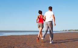 Pares jovenes que corren junto al lado del agua en la playa Hombre Imagen de archivo libre de regalías