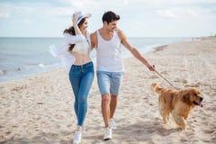 Pares jovenes que corren a lo largo de la playa con su perro Fotografía de archivo libre de regalías