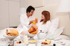 Pares jovenes que desayunan en cama Imágenes de archivo libres de regalías
