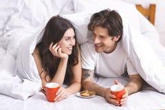 Pares jovenes que desayunan en la cama, ocultando debajo de la manta imagenes de archivo