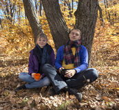 Pares jovenes que descansan en bosque del otoño Foto de archivo