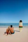 Pares jovenes que descansan sobre la playa Foto de archivo