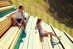 Pares jovenes que descansan sobre un banco, juventud, adolescentes, concepto de la moda Imagen de archivo libre de regalías