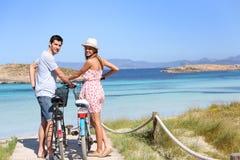 Pares jovenes que descubren la isla hermosa en las bicis Fotografía de archivo