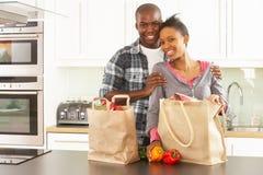 Pares jovenes que desempaquetan compras en cocina moderna fotografía de archivo libre de regalías
