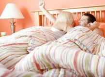 Pares jovenes que despiertan en cama Fotografía de archivo libre de regalías
