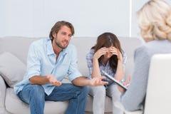 Pares jovenes que discuten y que lloran en el sofá Imagenes de archivo
