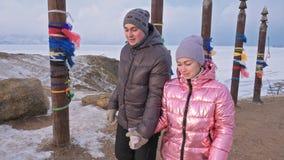 Pares jovenes que disfrutan de caminar al aire libre en montañas del top del invierno Polos rituales budistas con las cintas colo metrajes