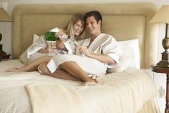 Pares jovenes que disfrutan de Champán en dormitorio Fotos de archivo libres de regalías