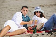 Pares jovenes que disfrutan de comida campestre en la playa Imagen de archivo