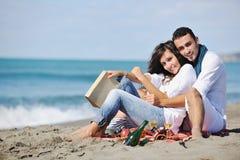 Pares jovenes que disfrutan de comida campestre en la playa Imágenes de archivo libres de regalías