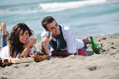 Pares jovenes que disfrutan de comida campestre en la playa Fotos de archivo libres de regalías