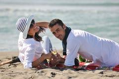 Pares jovenes que disfrutan de comida campestre en la playa Fotografía de archivo