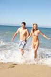 Pares jovenes que disfrutan de día de fiesta de la playa Fotos de archivo