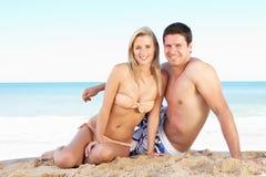 Pares jovenes que disfrutan de día de fiesta de la playa Imagenes de archivo