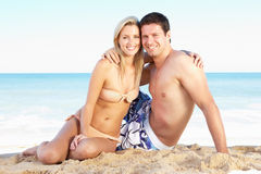 Pares jovenes que disfrutan de día de fiesta de la playa Imagen de archivo libre de regalías
