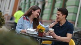 Pares jovenes que disfrutan de la fecha romántica en café de la calle metrajes