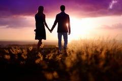 Pares jovenes que disfrutan de la puesta del sol Imagen de archivo