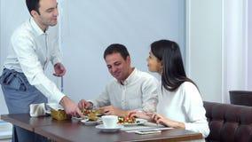 Pares jovenes que disfrutan de su almuerzo en el café cuando camarero que sirve más comida almacen de video